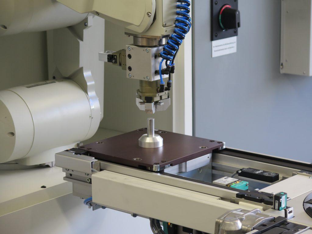 Ein Roboter am Portal des Bearbeitungszentrums entnimmt den Rohling vom Werkzeugtr?ger und setzt ihn in das Spannfutter ein bzw. wendet ihn f?r beidseitige Bearbeitung. (Bild: Feintechnikschule Schwenningen)