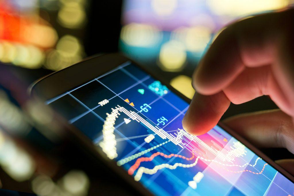 A businessman using a mobile phone to check stock market data. (Bild: ©James-Thew/Fotolia.com)