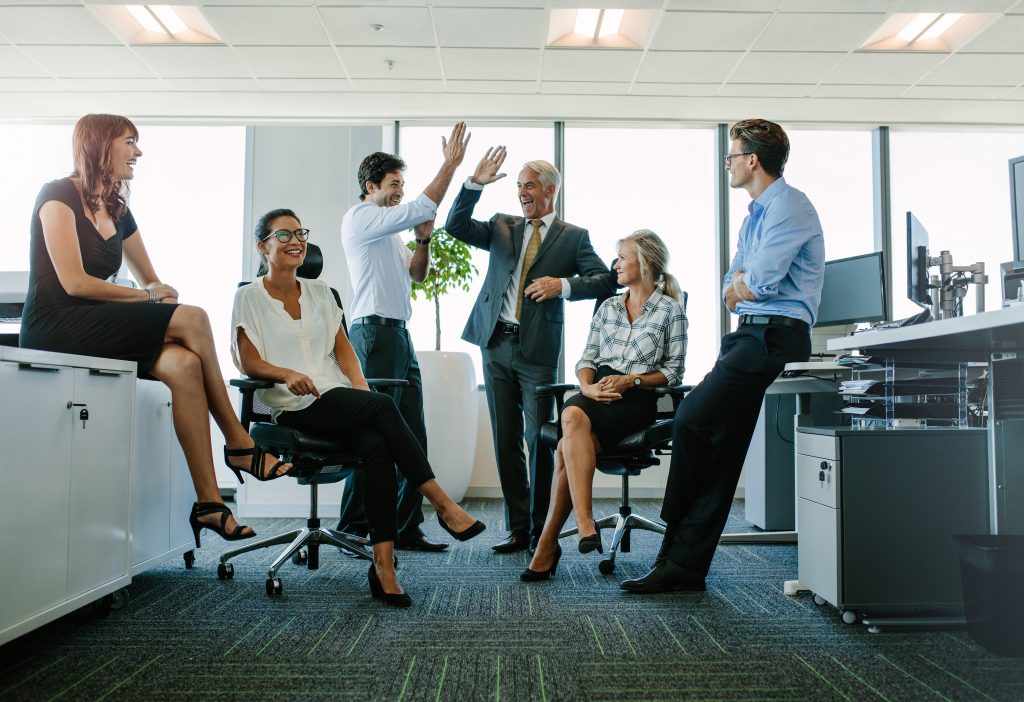 Two cheerful business people giving high-five while their colleagues looking at them and smiling. Business team enjoying success at office (Bild: ©Jacob_Lund/Fotolia.com)