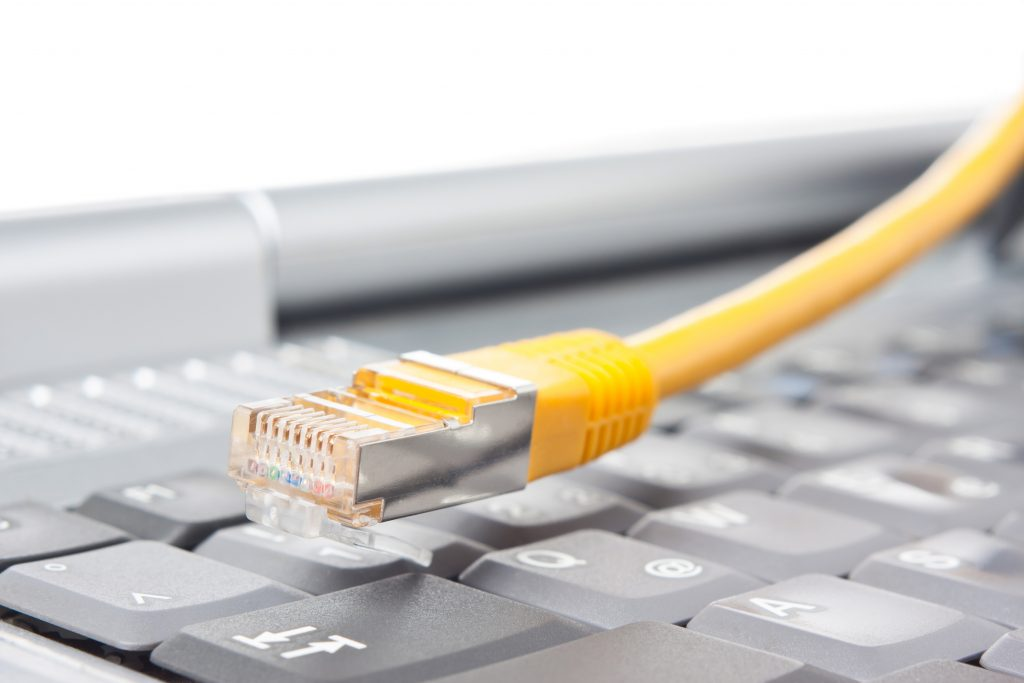 Macro of a yellow network cable in front of a keyboard (Bild: ©Heiko Barth/Fotolia.de)
